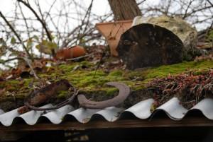 Stilleben mit Hufeisen und Steigbügel auf dem Schuppendach